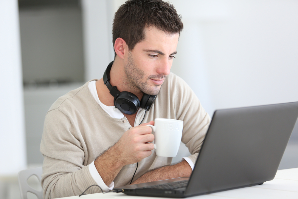 Man sitting in front of laptop working remotely